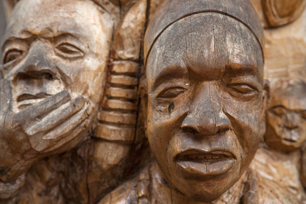 Faces carved out of the columns of the Case | Bandjoun chefferie | Cameroon