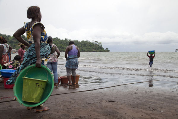 Woman waiting for the guys to carry the fish to shore | Limbe en Batoke stranden | Kameroen