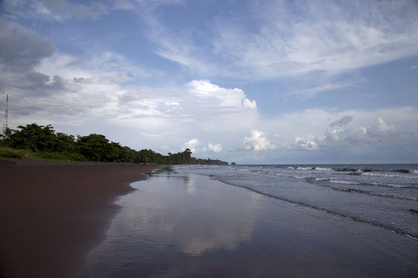 Foto di Clouds reflected in the sea at the chocolate-coloured beach of Batoke - Camerun - Africa