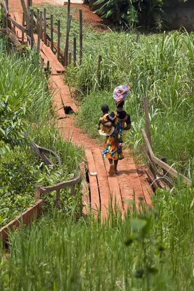 Cameroonian woman walking a wooden bridge at the foot of Mount Eloundem | Mount Eloundem | Cameroon