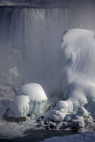 Close-up of the American Falls with thick ice cover over the boulders | Frozen Niagara Falls | Canada
