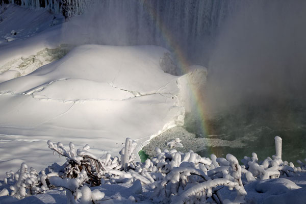 A rainbow over the ice cap on the Niagara river at the base of the Horseshoe Falls | Frozen Niagara Falls | Canada