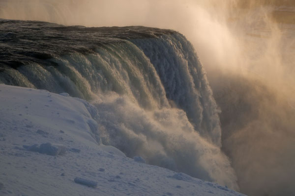 Afternoon sunlight filtering through the spray of the American Falls | Frozen Niagara Falls | Canada