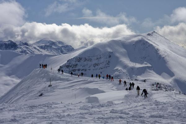 Skiers and boarders walking on a ridge to find a challenging downhill slope | Lake Louise skiing | Canada