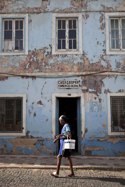 Foto de Early morning in the old part of Mindelo with woman walking past a shop - Cabo Verde - Africa