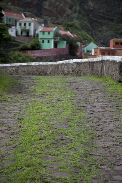The stony road with grass and Fontainhas in the background | Ponta do Sol to Chã de Igreja | 维德角群岛