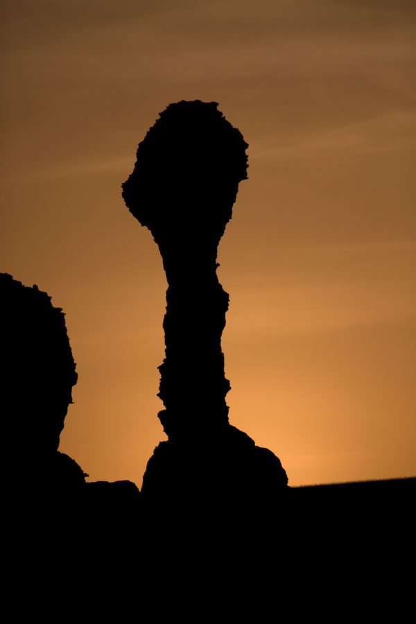 Foto de Silhouette of a bizarre rock formation at sunsetAbaike Tassili - Chad