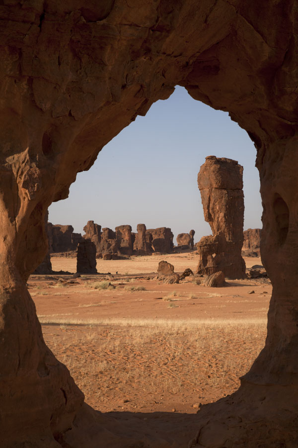 Looking through a hole in a rock with other formations in the background | Abaike Tassili | Chad
