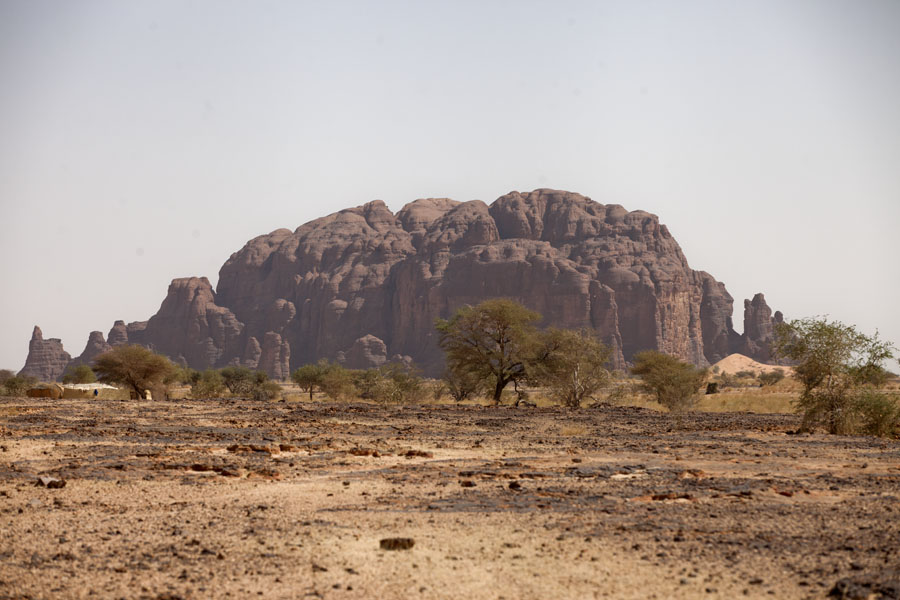 Big rock formation with trees at the west side of the Terkei massif | Terkei amphitheatre west | Chad