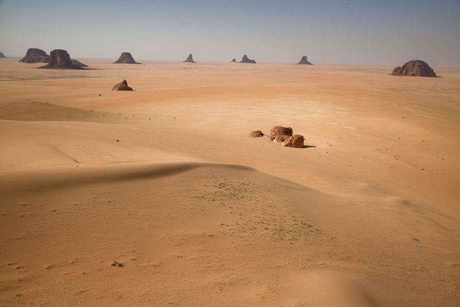 Foto van View over a sandy plain with isolated rock formations - Tsjaad