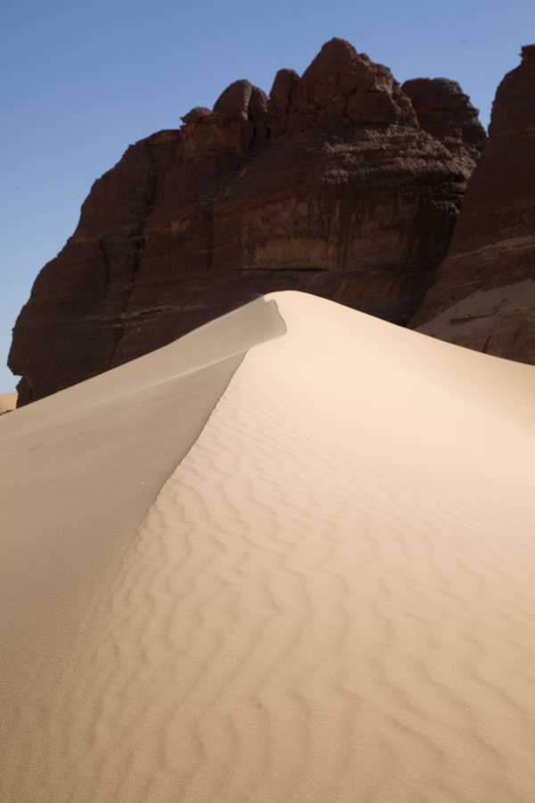 Picture of Crest of sand dune in front of a rock formation - Chad