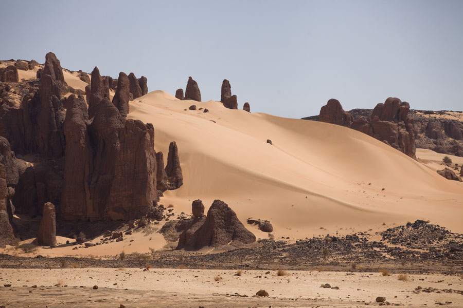 Foto di Rock formations encompassing a huge sand dune - Ciad - Africa