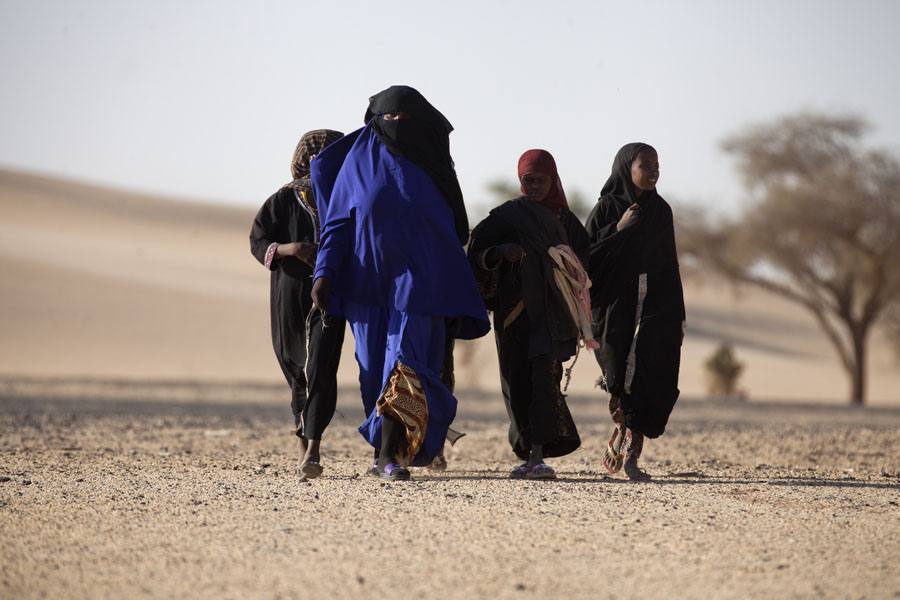 Woman and girls approaching to sell souvenirs in northern Chad | Ciadiani | Ciad