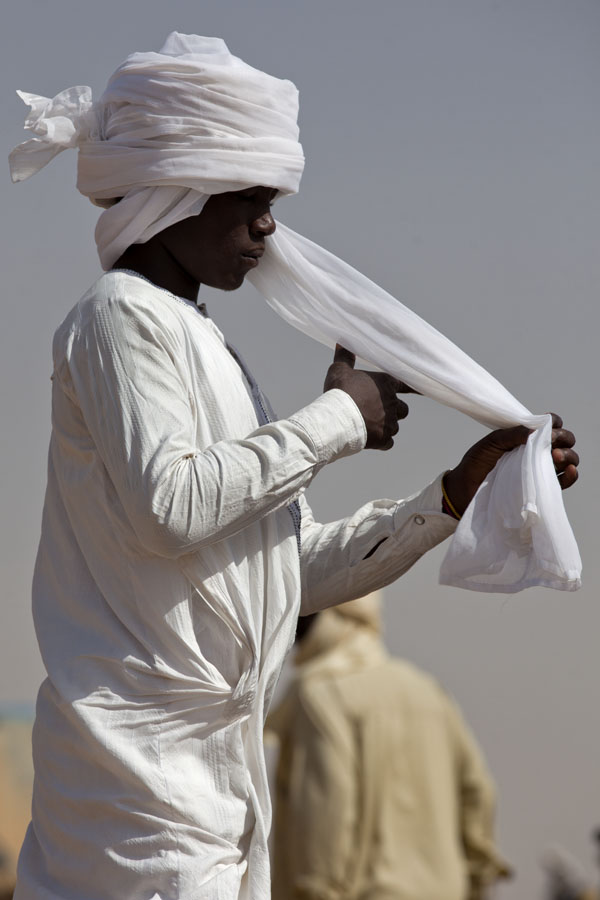 Man folding his headdress at one of the many wells in Kalaita, eastern Chad | Tsjadiërs | Tsjaad
