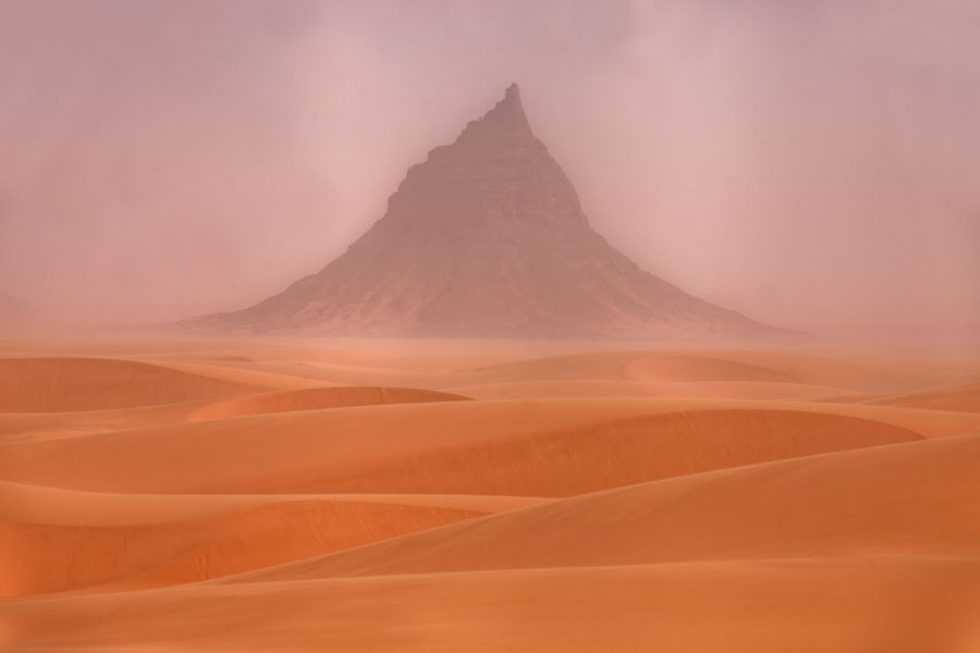Sand dunes and pointy peak of a mountain in the background | Eyo demi | Ciad