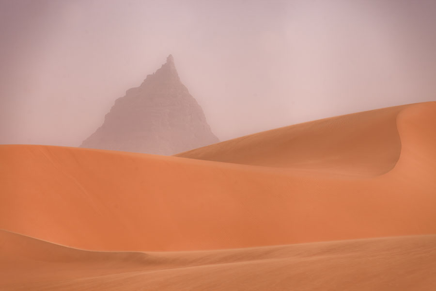 Curved sand dunes with mountain peak in the desert | Eyo demi | 查德