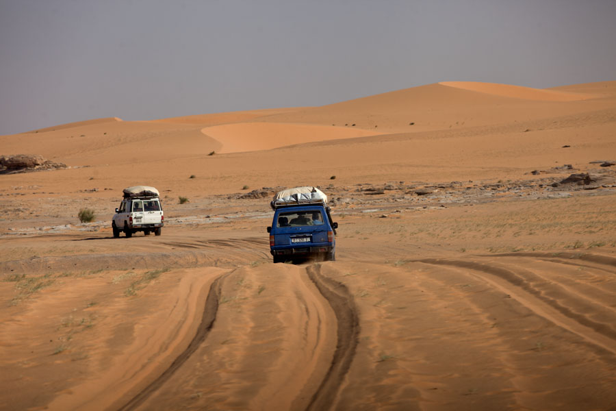 Convoy of Landcruisers working their way through deep sand in the desert | Koraa | Chad