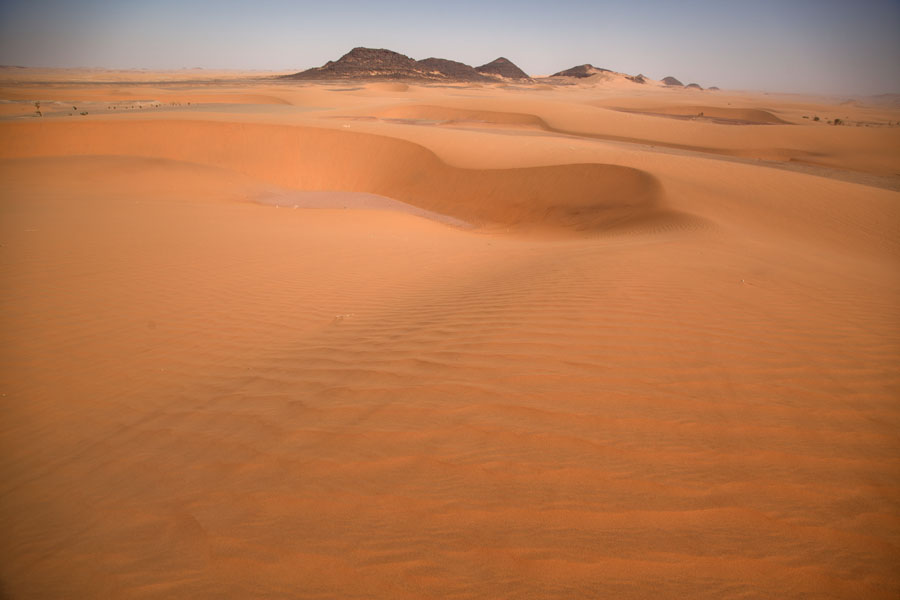 Foto de View from a sand dune with rocky mountains at the horizonKoraa - Chad