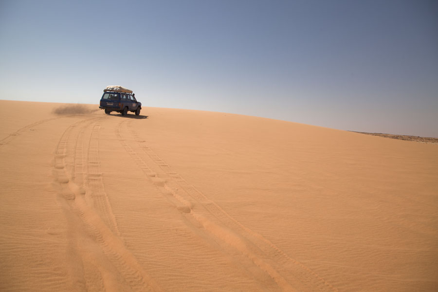 Foto van Land cruiser driving up a sand dune in the desertKoraa - Tsjaad