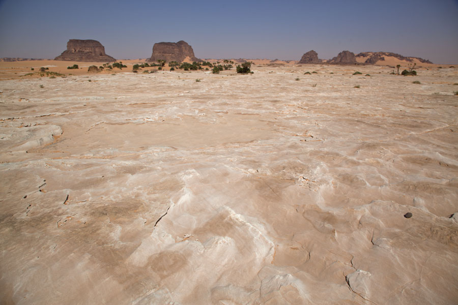 White-crusted earth and plain with rock formations in the distance | Koraa | Chad