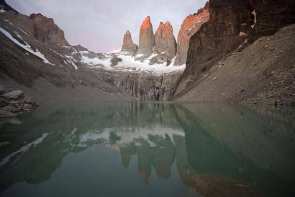 Pink Torres del Paine reflected in the perfectly tranquil waters of the glacier lake at sunrise | Torres del Paine | Chili