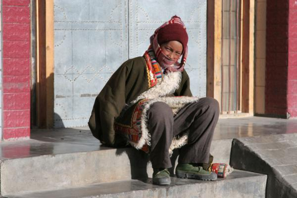 Amdo boy sitting on stairs in the afternoon sun in Mato | Amdo Tibetans | China