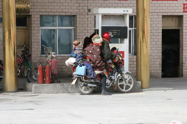 Amdo family in their traditional dresses on a motorbike | Amdo Tibetans | China