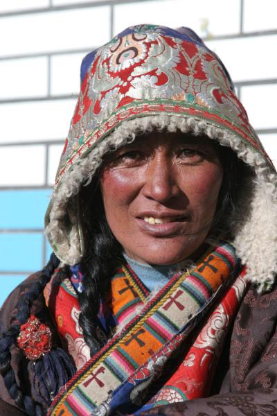 Tibetan woman under a colourful traditional Tibetan hood | Amdo Tibetans | China