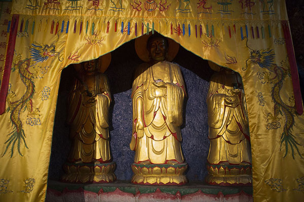 Golden Buddha statues partly hidden behind cloth in a cave | Baoshi mountain | China