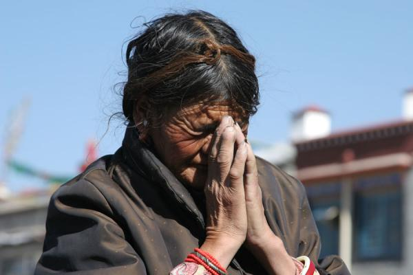 Picture of Barkhor kora (China): Praying in front of the Jokhang temple: old woman