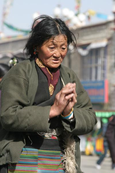 Picture of Barkhor kora (China): Tibetan woman stopping for prayer on the Barkhor circuit