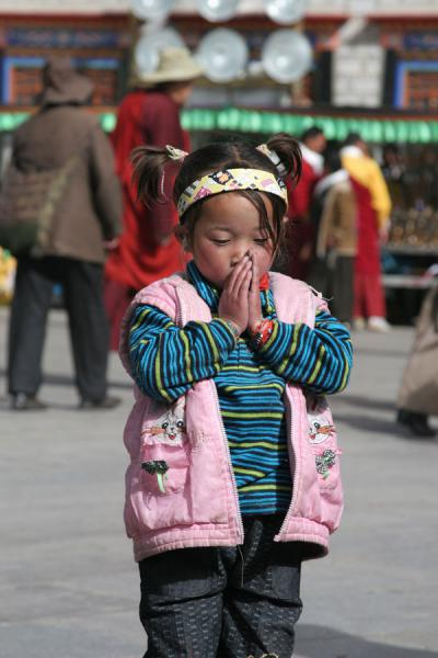 Picture of Barkhor kora (China): Young Tibetan girl praying in front of the Jokhang temple