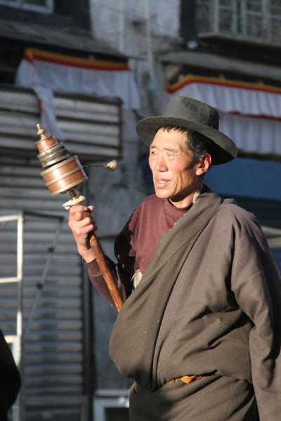 Picture of Barkhor kora (China): Man with prayer wheel walking the Barkhor kora in the early morning