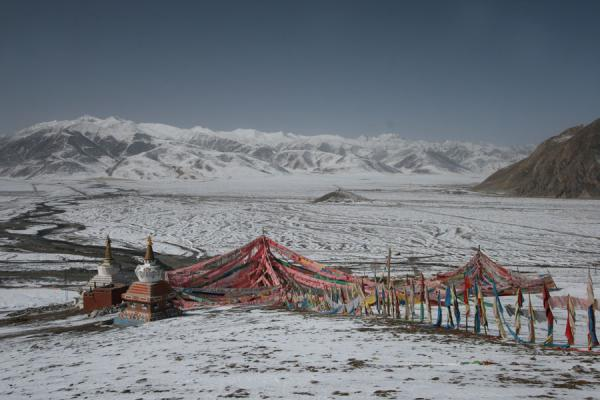 Prayer flags and snowy mountains at Batang sky burial site | Batang hemelbegrafenis | China