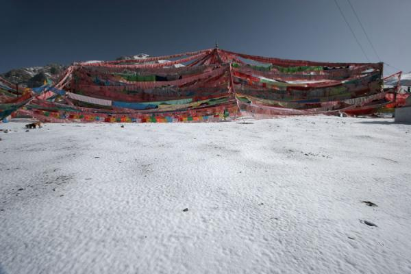 Prayer flags, snow and an intensely blue sky | Batang hemelbegrafenis | China