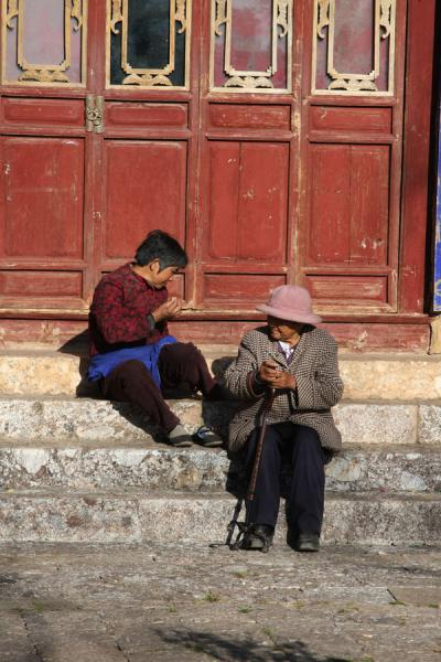 Two old women sitting in the sun near the Black Dragon Pool | Black Dragon Pool | China