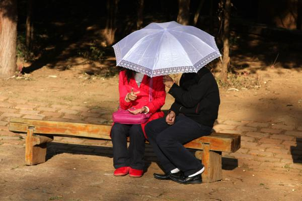 Sitting cosily under an umbrella in Black Dragon Pool park | Black Dragon Pool | China