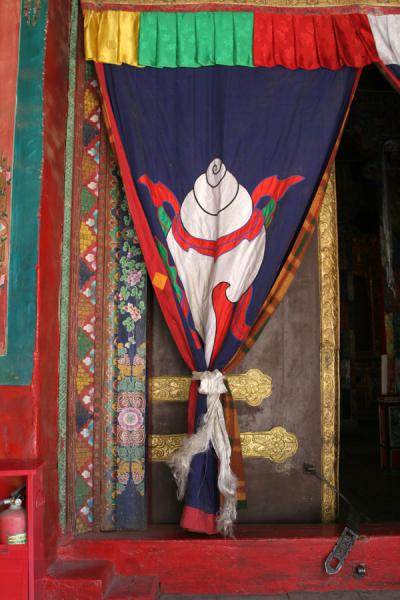 Door to Tsozong monastery with the symbolical conch shell on the curtain | Draksum-Tso | China