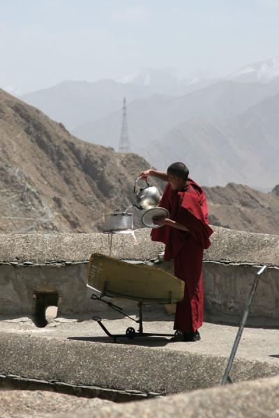 Monk pouring water in solar-heated pot | Drepung monastery | China