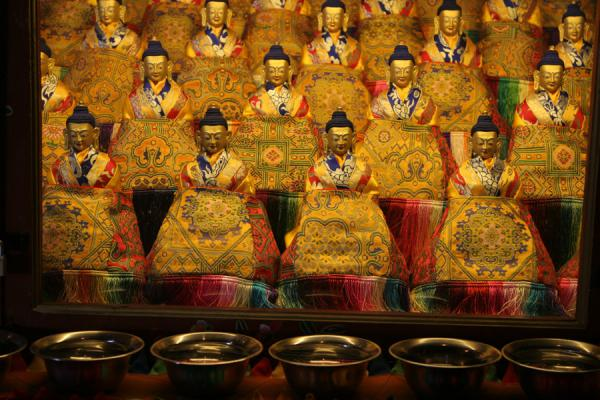 Close-up of small golden Buddhas and butter lamp bowls | Drepung monastery | China