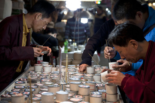 Picture of Flowers, fish, birds and insects market (China): Men examining small boxes with insects at an insect stall at the market