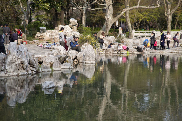 People relaxing at rocks near a pond in Fuxing Park | Parc Fuxing | Chine