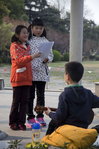 Foto van Little boy playing guitar for two singing girlsFuxing Park - China
