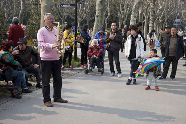 Picture of Man playing trumpet drawing a crowd in Fuxing park