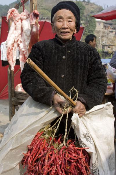 Old woman selling chillies - note the holes in her ears | Gedong market | China