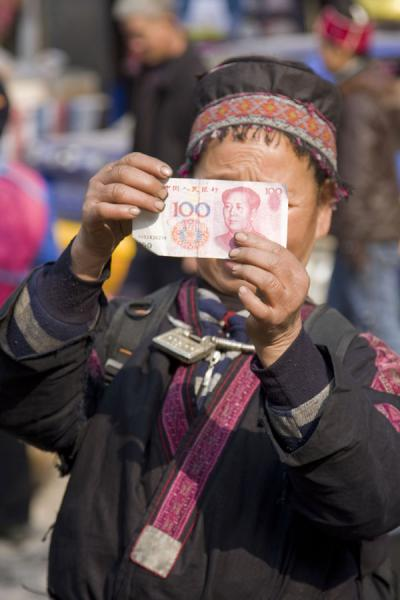 Picture of Gedong market (China): Market woman checking a 100 Yuan note