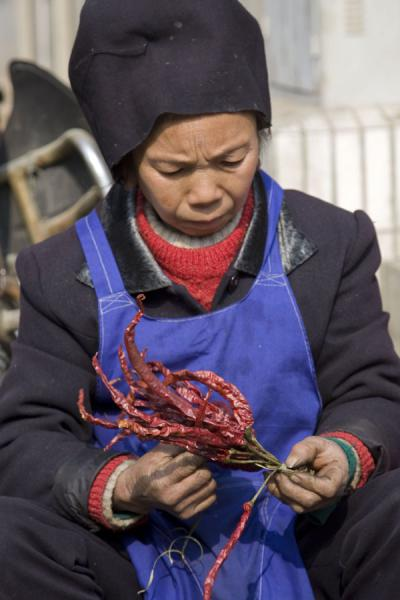 Market woman tying chillies together | Gedong market | China