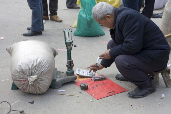 Picture of Gedong market (China): Street vendor calculating a price