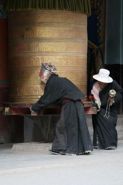 Tibetan pilgrims turning one of the large prayer wheels of Gyanak Mani | Gyanak Mani | China
