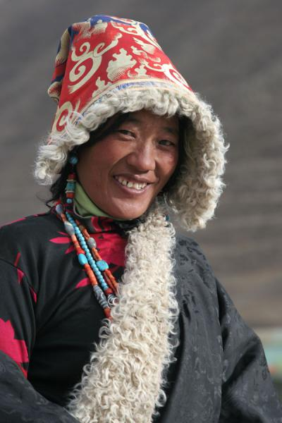 Smiling pilgrim in traditional dress on her kora around Gyanak Mani | Gyanak Mani | China